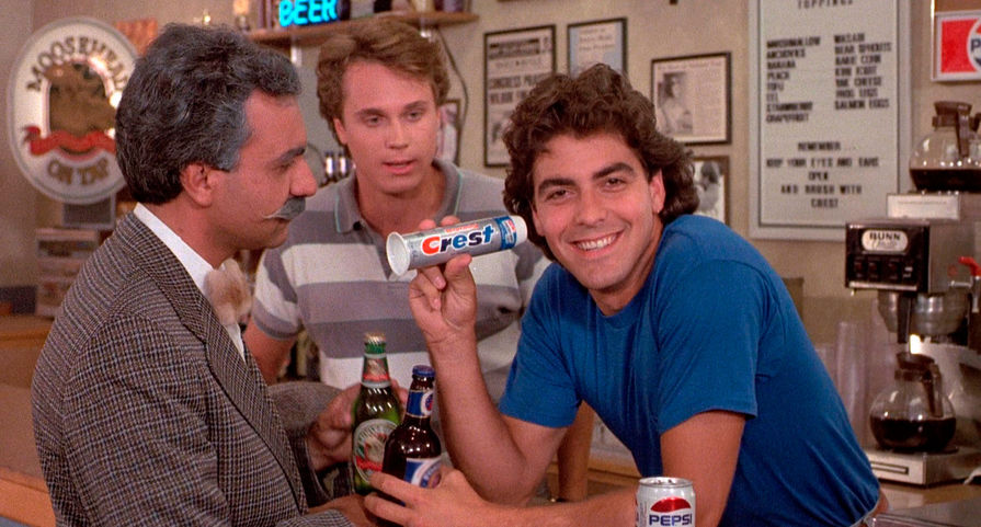 Джордж Тимоти Клуни родился 6 мая 1961 году в американском Кентукки. В школьные годы будущий актер страдал от генетической болезни, из-за которой у него была парализована половина лица. Впоследствии, уже став звездой, артист признавался, что то время было худшим в его жизни: одноклассники дали ему прозвище «Франкенштейн», всячески дразнили и издевались. Впрочем, по словам Клуни, это сделало его только сильнее. Посвятить себя актерству Джордж решил далеко не сразу: изначально он хотел стать юристом, а также пробовался на спортивном попроще. Однако с мечтой о карьере профессионального бейсболиста у него не сложилось, и уже в середине 80-х он дебютировал в кино. На фото Клуни в фильме «Возвращение помидоров-убийц» (1988)