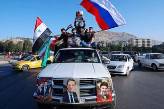 Сторонники сирийского правительства в Дамаске с флагами Сирии, Ирана и России во время демонстрации после ракетных ударов США, Великобритании и Франции, 14 апреля 2018 года