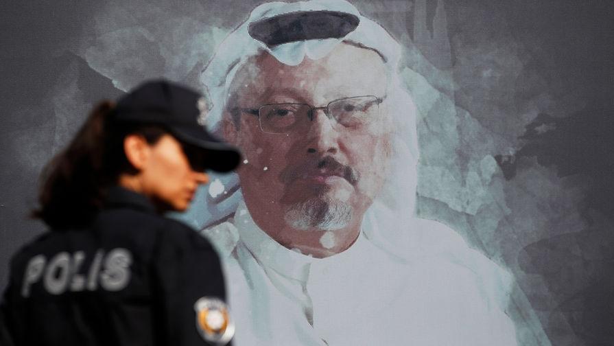 Сотрудница турецкой полиции около портрета Джамаля Хашукджи перед началом церемонии в годовщину убийства журналиста возле консульства Саудовской Аравии в Стамбуле, 2 октября 2019 года