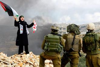 Палестинская женщина и израильские солдаты в Секторе Газа