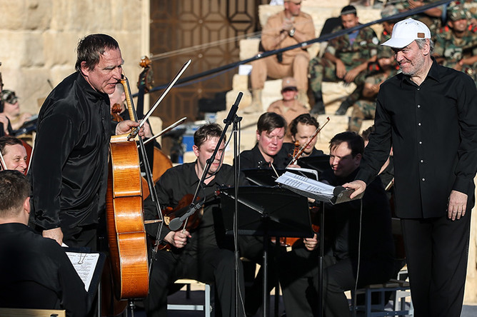 Сергей Ролдугин (слева) и дирижер Валерий Гергиев (справа) во время концерта «С молитвой о Пальмире. Музыка оживляет древние стены» Симфонического оркестра Мариинского театра на площадке Римского амфитеатра в Пальмире, 2016 год