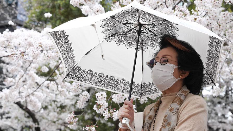 Женщина гуляет в парке Тидоригафути в Токио, март 2021 года