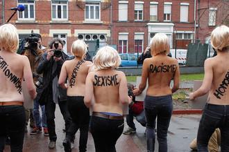 Акция активисток движения FEMEN против Марин Ле Пен. На спинах женщин надписи: «расизм», «сексизм» и «ксенофобия»