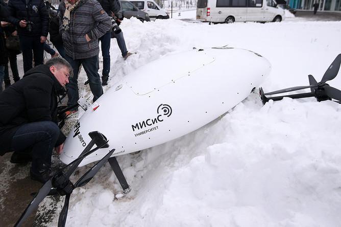 Техники осматривают прототип электролета после падения в сугроб во время тестового полета в рамках презентации лаборатории городских полетов, 7 декабря 2018 года