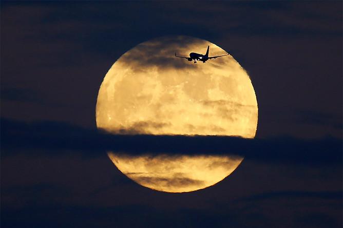 Самолет на фоне Луны в небе над Сан-Диего