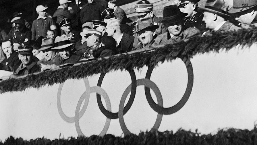 Скучающий Адольф Гитлер на хоккейном матче между командами Великобритании и Венгрии во время зимних...