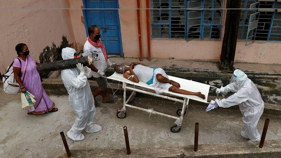 Медики перевозят зараженного коронавирусом мужчину в реанимацию в городе Бхагалпур, август 2020 года