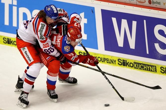 Хоккеист сборной России борется за шайбу с чехом в третьем матче на Евротуре
