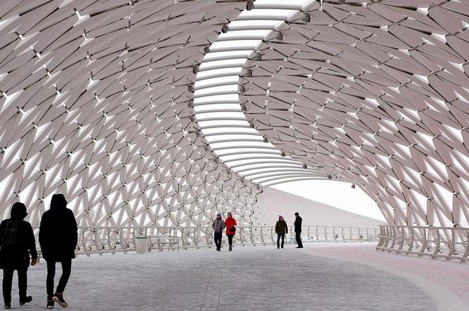 Прохожие идут по пешеходному мосту через реку Ишим в Нур-Султане (ранее Акмолинск, Целиноград, Акмола, Астана?)