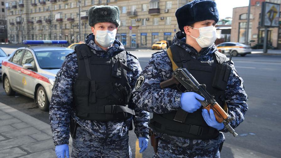 Сотрудники Росгвардии в медицинских масках во время проверки соблюдения домашнего режима на одной из улиц в Москве.