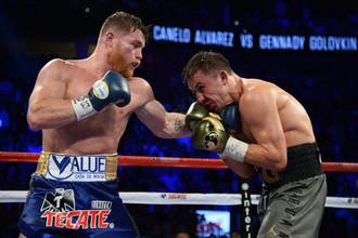 Сауль Альварес (слева) атакует Геннадия Головкина в первом бою