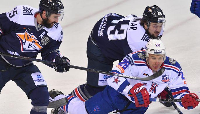 Игроки «Металлурга» Данис Зарипов (слева) и Ян Коварж в борьбе с защитником СКА Андреем Зубаревым