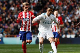 Нападающий «Реала» Криштиану Роналду борется за мяч с форвардом «Атлетико» Антуаном Гризманном