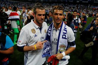 Нападающие мадридского «Реала» Криштиану Роналду и Гарет Бэйл празднуют победу в чемпионате Испании после выездного матча против «Малаги» в последнем туре Примеры