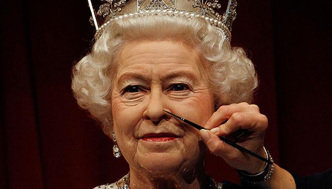 Сотрудник музея с кисточкой и фигурой британской королевы Елизаветы II, 2012 год