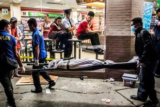 Сотрудники полиции и похоронной службы уносят тело мужчины, убитого на одной из улиц в Маниле, Филиппины