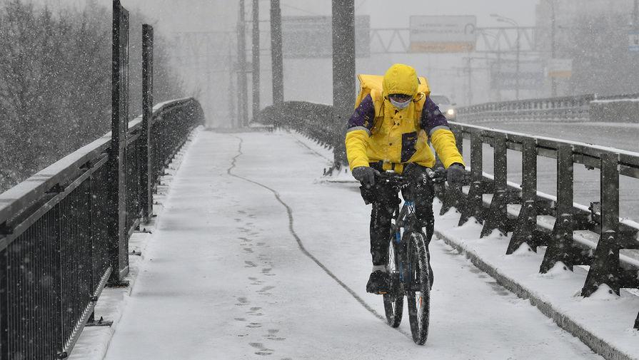 Курьер на велосипеде на улице в Москве, 31 марта 2020 года