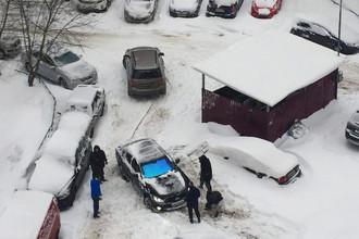 Жители Москвы пытаются вытащить из сугроба автомобиль, 4 февраля 2018 года