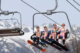 Участники мероприятия по спуску с горы в купальниках, проходящего в рамках фестиваля BoogelWoogel, на канатной дороге горнолыжного курорта «Роза Хутор» в Сочинском национальном парке