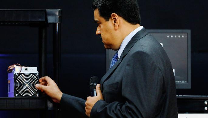 Президент Венесуэлы Николас Мадуро с компьютером для майнинга во время запуска национальной...