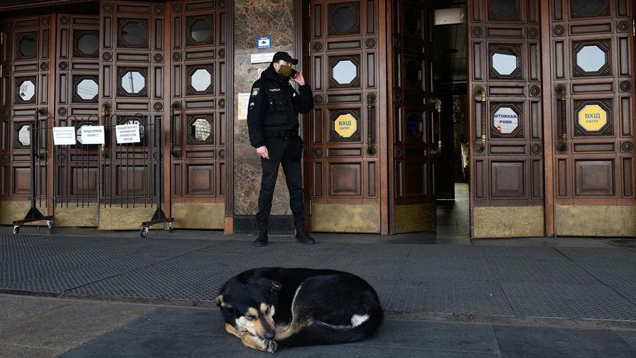 Сотрудник полиции у входа в здание центрального железнодорожного вокзала в Киеве, 18 марта 2020 года