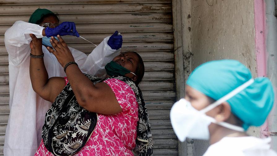 Врач пытается взять мазок на коронавирус у жительницы Мумбая, сентябрь 2020 года