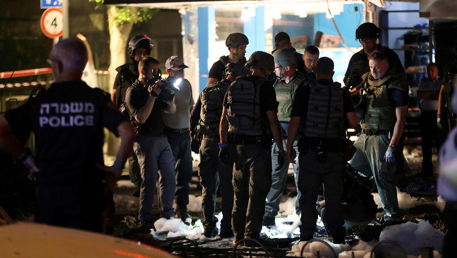 Сотрудники сил безопасности после обстрела израильского города Холон, 11 мая 2021 года