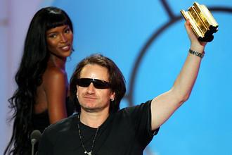 U2 вокалист Боно держит свою музыкальную награду, врученную британской топ-моделью Наоми Кэмпбелл во время церемонии вручения музыкальных наград NRJ в Каннах. 2005 год