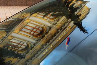 Здание Центрального банка России на Неглинной улице в Москве в отражении на лобовом стекле автомобиля