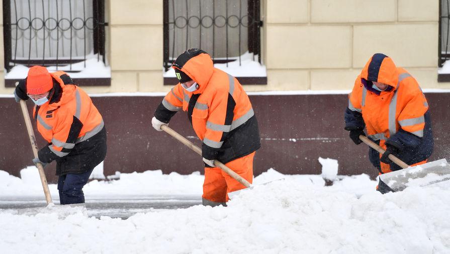 Сотрудники коммунальной службы убирают снег на Красноказарменной улице в Москве, 13 февраля 2021 года