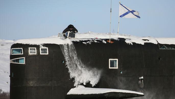Один из членов экипажа очищает от снега рубку атомного ракетного подводного крейсера стратегического назначения проекта 667БДРМ «Дельфин» К-18 «Карелия» на причале в Мурманской области, 2021 год