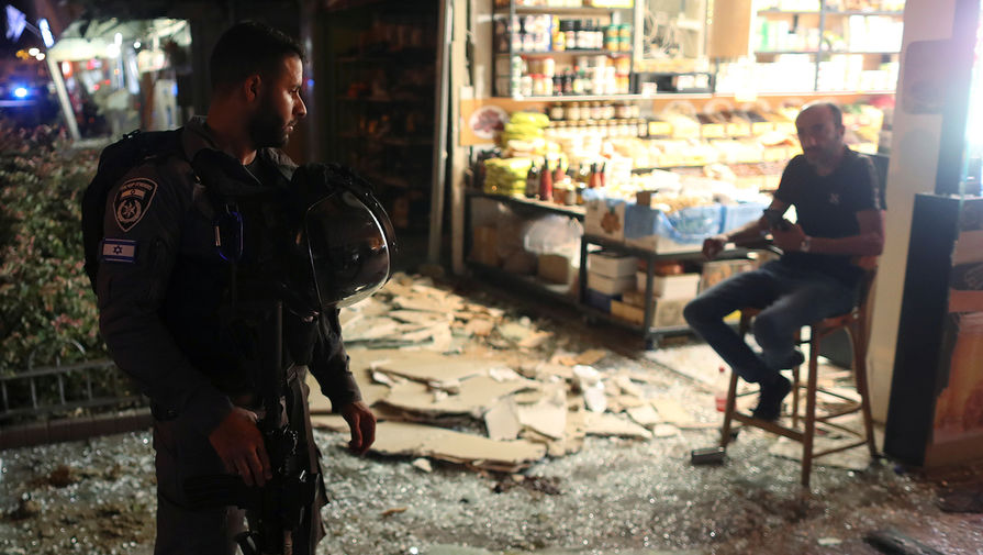 Сотрудник сил безопасности разговаривает с мужчиной на месте попадания ракеты, выпущенной из сектора Газа, в Холоне, 11 мая 2021 года