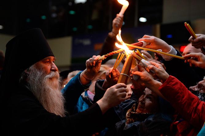 Викарий Патриарха Московского и всея Руси епископ Дмитровский Феофилакт зажигает свечи верующих от свечи с Благодатным огнем в аэропорту Внуково