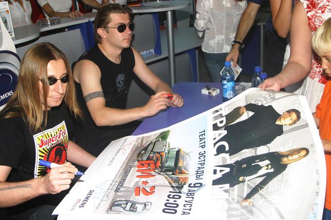 Участники группы «Би-2» Лева и Шура подписывают плакаты для поклонников. Волгоград, 2005