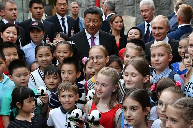 Президент России Владимир Путин и председатель КНР Си Цзиньпин во время церемонии передачи Московскому парку двух больших панд, 5 июня 2019 года