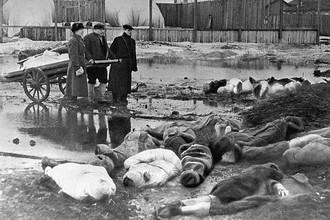 Трое мужчин хоронят умерших в дни блокады в Ленинграде