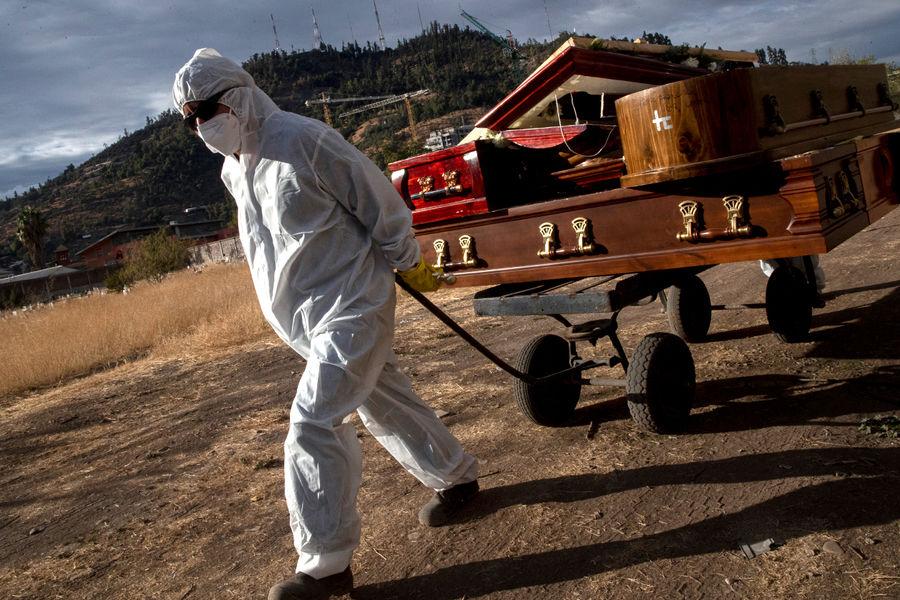 Сотрудник кладбища в Сантьяго, Чили, выполняет свою работу во время пандемии коронавируса, 21 апреля 2021 года