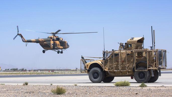 Вертолет национальной армии Афганистана и бронемашина ВС США на авиабазе в Кандагаре
