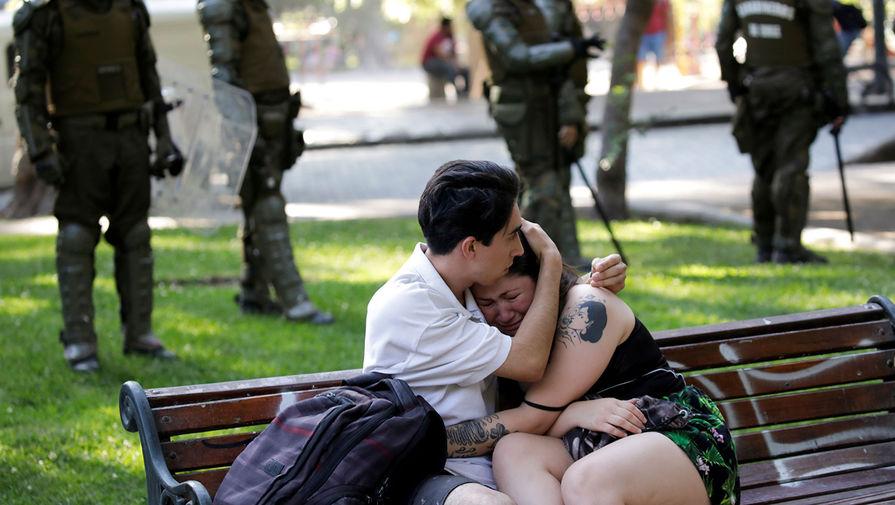 Молодой человек утешает подругу во время акции протеста против правительства Чили в Сантьяго, 16 декабря 2019 года