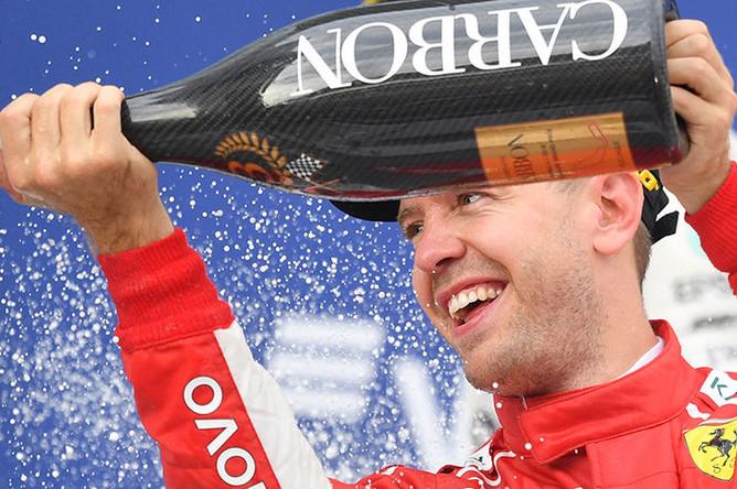 Гонщик команды «Феррари» Себастьян Феттель, занявший третье место, на церемонии награждения призеров российского этапа чемпионата мира по кольцевым автогонкам в классе «Формула-1», 30 сентября 2018 года