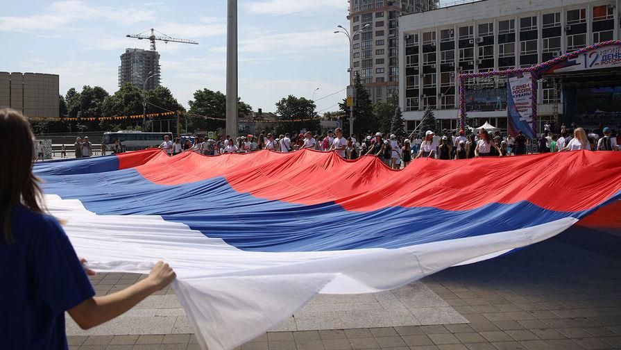 Участники флэшмоба «Я люблю Россию» развертывают огромный триколор на Главной городской площади в Краснодаре