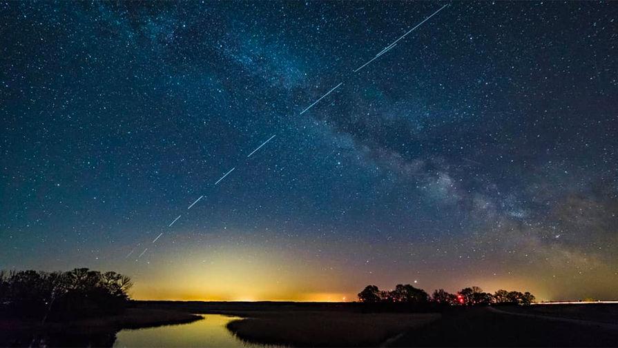 Cпутники связи Starlink компании SpaceX Илона Маска проходят по орбите Земли в небе над городом Тангермюнде, Германия, 25 апреля 2020 года