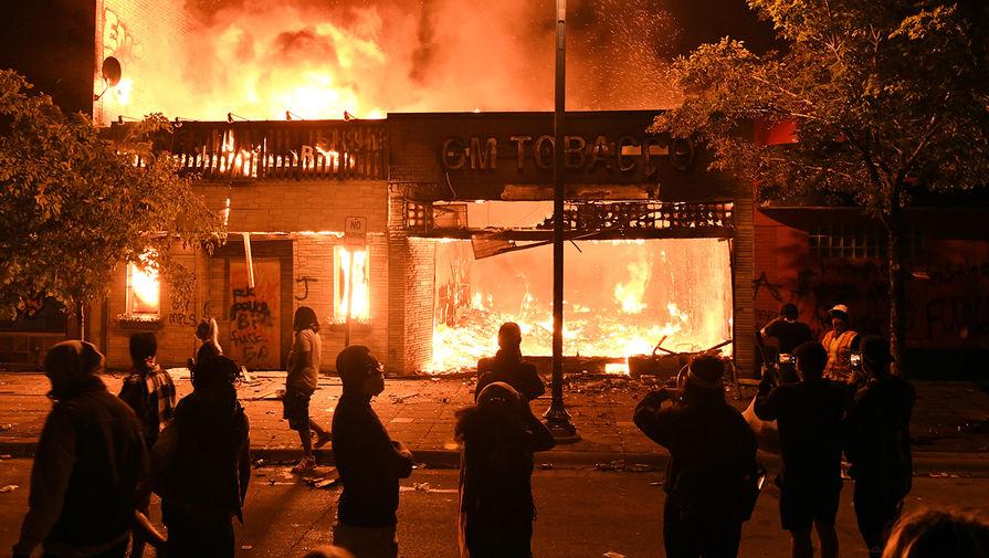 Горящий табачный магазин около полицейского участка во время беспорядков в Миннеаполисе, 28 мая 2020 года