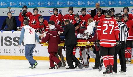 Словацкого игрока Патрика Лужу увозят на носилках со льда в матче с Канадой