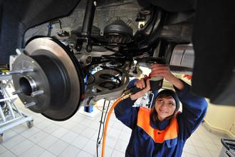 Студентка колледжа во время практических занятий в автомобильной мастерской