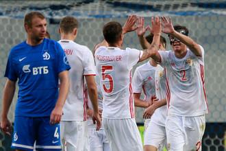 Защитник «Динамо» Владимир Рыков расстроен из-за пропущенного гола, а на его фоне игроки сборной России отмечают забитый мяч