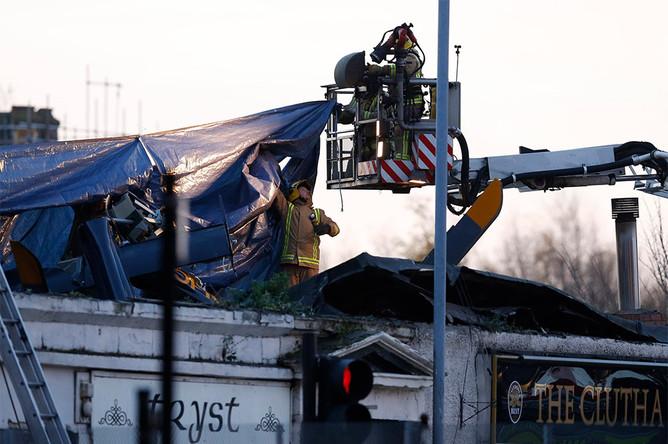 Спасатели работают на месте крушения вертолета в Глазго