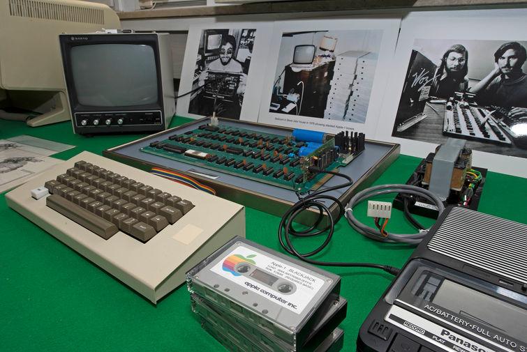 <b>Apple 1 (1976)</b><br><br> Apple 1, разработанный Стивом Возняком, является первым компьютером компании и в принципе первым продуктом «яблочного» бренда. Изначально Возняк создавал его для личного пользования, но его другу и коллеге Стиву Джобсу пришла в голову идея продавать устройство массовому потребителю. Apple 1 продавался в виде полностью укомплектованных системных плат по цене в $666,66. Предполагается, что такая стоимость появилась неслучайно — якобы Возняку нравились повторяющиеся цифры, а еще изначально сооснователи Apple продавали компьютер в местный магазин за $500, а новая сумма отражала наценку в размере одной третьей от этой цены. На фото Apple 1 под номером 46 на аукционе в Германии