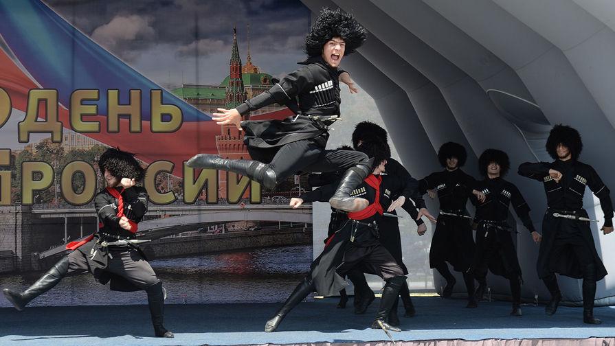 Участники ансамбля песни и танца «Заманхо» выступают на праздничном концерте, посвященном Дню России, на площади перед мечетью «Сердце Чечни» в Грозном