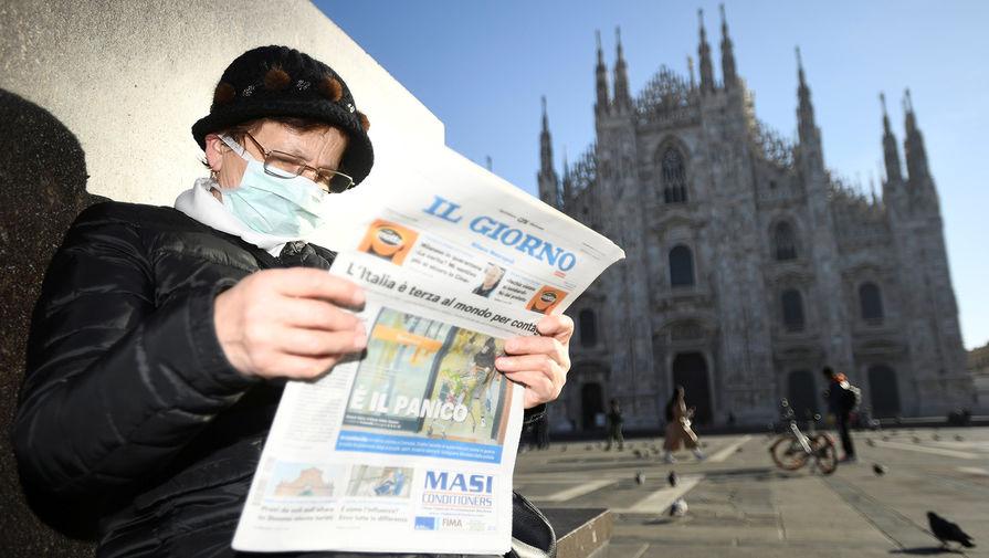 Жительница Венеции читает свежую газету на площади у Кафедрального собора в Милане, который был закрыт в связи с вспышкой коронавируса в Италии, 24 февраля 2020 года